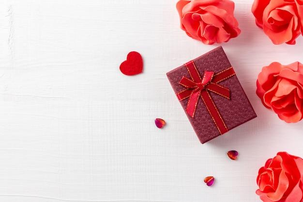 Composizione romantica con scatola rossa presente e cuori per san valentino su legno bianco