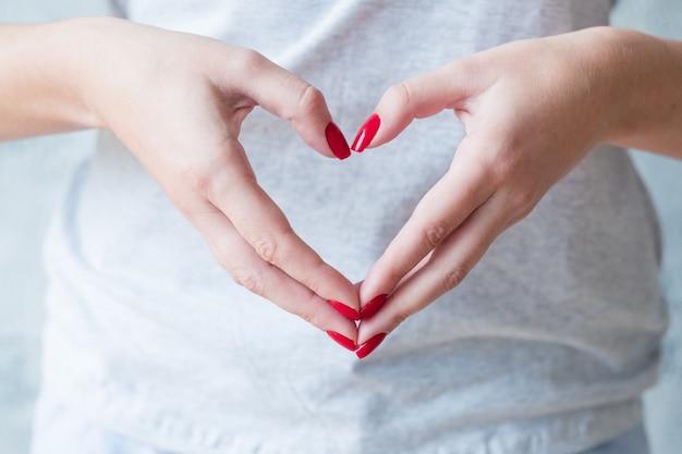 Concetto romantico. mani della donna che mostrano il simbolo del cuore di amore.