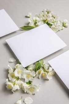 Cartolina di congratulazioni romantiche con fiori di gelsomino freschi naturali allegati su uno sfondo grigio, spazio copia