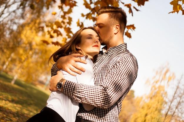 Coppia romantica nel parco d'autunno - giornata di sole - amore, relazione e concetto di datazione