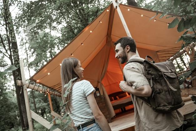 Coppia romantica in campeggio all'aperto e in piedi nella tenda glamping. felice l'uomo e la donna in una romantica vacanza in campeggio. l'uomo con lo zaino con la sua ragazza millennial è arrivato al sito di glamping.
