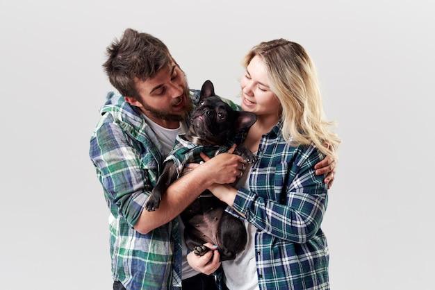 La coppia romantica in abbigliamento casual si diverte con il loro cane bulldog francese sul muro bianco