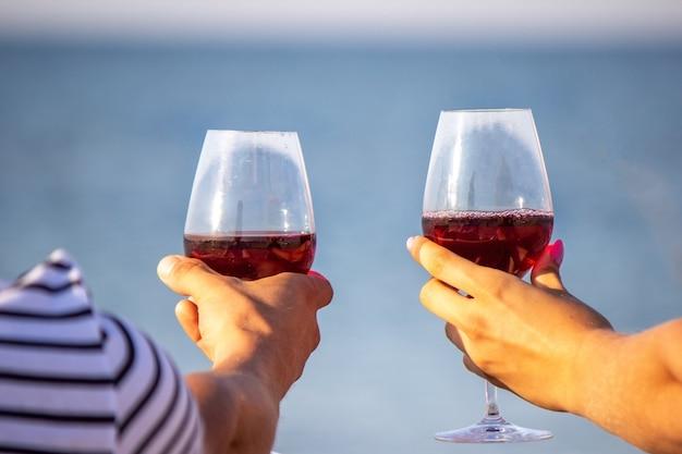 Coppia romantica gustando il vino in riva al mare