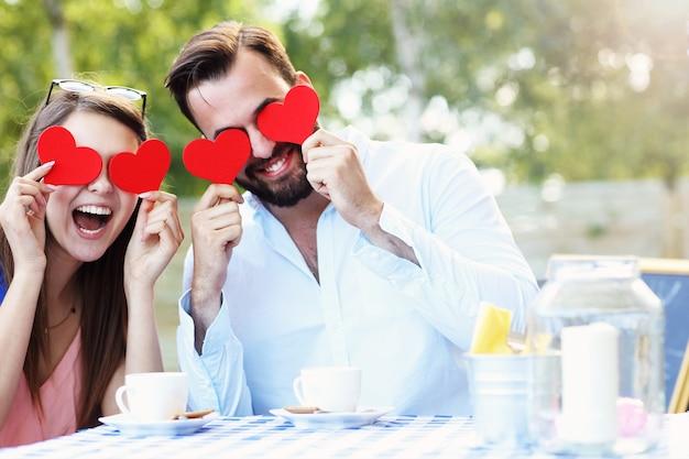 Coppia romantica che tiene i cuori caffè