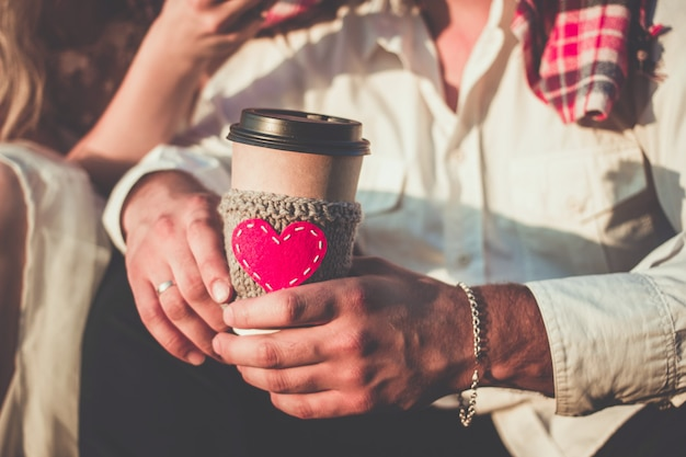 Coppia romantica che si abbraccia mentre fa un picnic tazza da caffè accogliente manica a maglia con cuore rosso in feltro