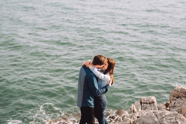 Coppia romantica sta baciando vicino al mare blu.