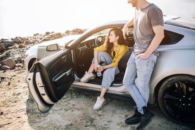 La coppia romantica è in piedi vicino a una muscle car sulla spiaggia. il bell'uomo barbuto e una giovane donna attraente hanno una storia d'amore.