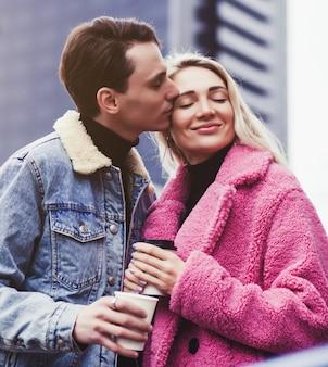 Coppie romantiche che baciano in città, tenendo le tazze di caffè