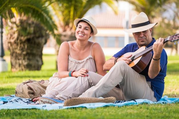 Coppia romantica uomo e donna anziano adulto a suonare la chitarra in una serenata per amore e relazione. attività di amicizia all'aperto insieme per il tempo libero per belle persone allegre che si godono la giornata e tye