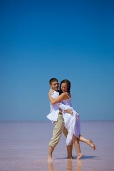 Una coppia romantica un uomo e una donna in abiti bianchi ballano su un lago rosa in una giornata di sole,
