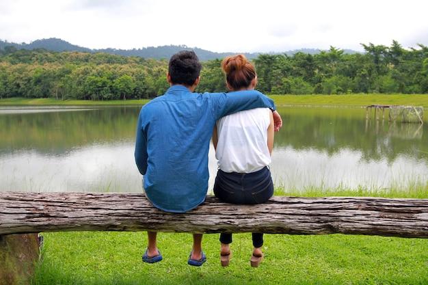 Coppia romantica seduta sul legno e godendo della vista di un tranquillo lago