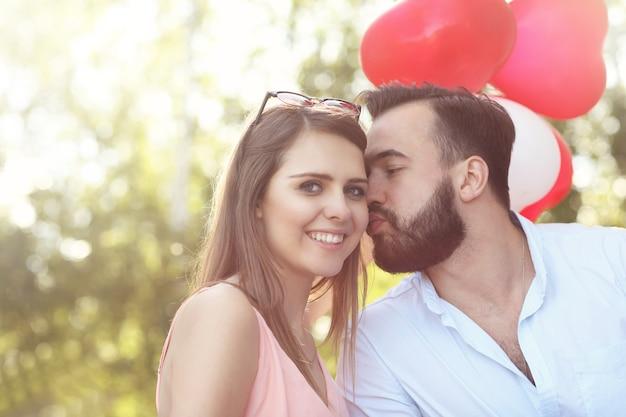 Una coppia romantica in piedi fuori con palloncini