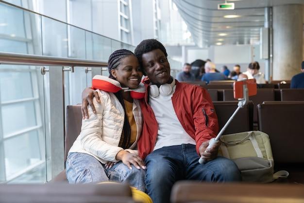 Le coppie romantiche prendono selfie nella lounge dell'aeroporto prima del volo Foto Premium