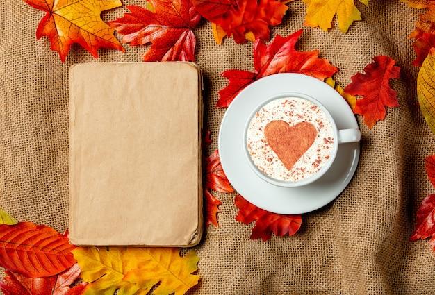 Romantica tazza di caffè e libro con foglie autunnali su sfondo di tela. vista dall'alto