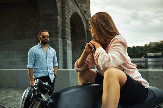 Appuntamento romantico in moto. la giovane donna si siede su una motocicletta e guarda l'uomo che viene da lei