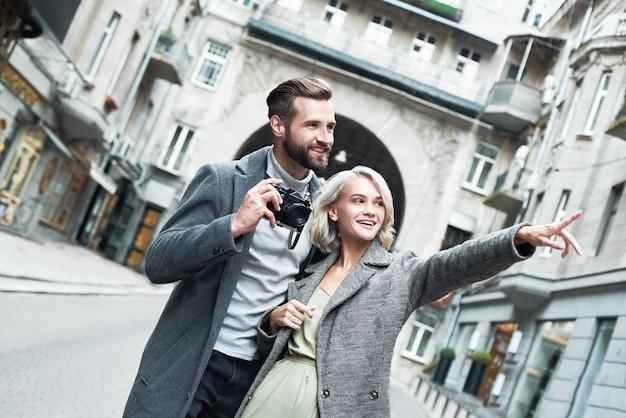 Appuntamento romantico all'aperto giovane coppia in piedi sull'uomo di strada della città che tiene la macchina fotografica mentre donna