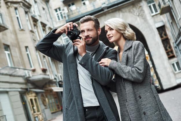 Appuntamento romantico all'aperto giovane coppia che cammina per la strada della città scattando foto con la fotocamera sorridente