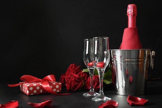 Appuntamento romantico con spumante, regalo, bouquet di rose rosse su fondo nero. celebrazione per il giorno di san valentino.