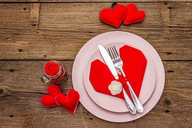 Romantico tavolo da pranzo con piatti e tovagliolo a forma di cuore