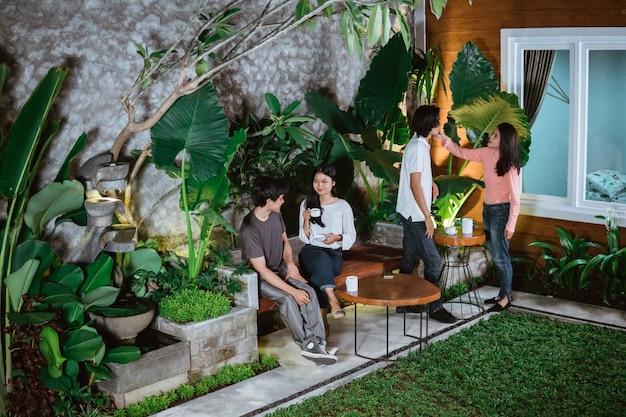 Romantico doppio appuntamento di coppie adolescenti che chiacchierano insieme nel giardino di casa