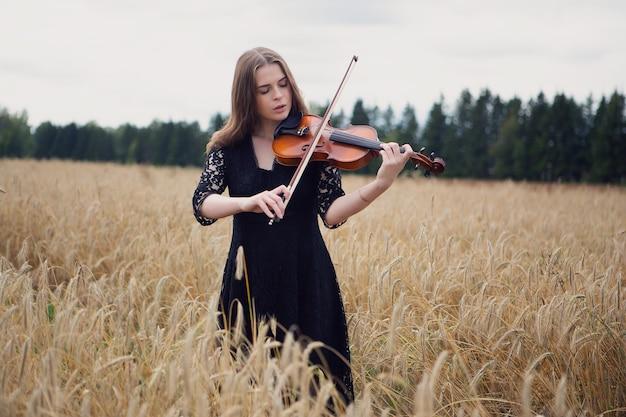 Violinista femminile romantico che gioca su un campo di grano