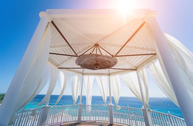 Gazebo romantico sulla spiaggia con il mare azzurro