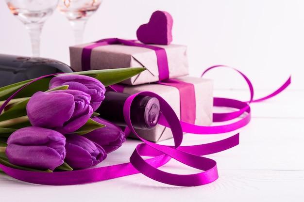 Regali romantici con fiori e vino sul muro bianco