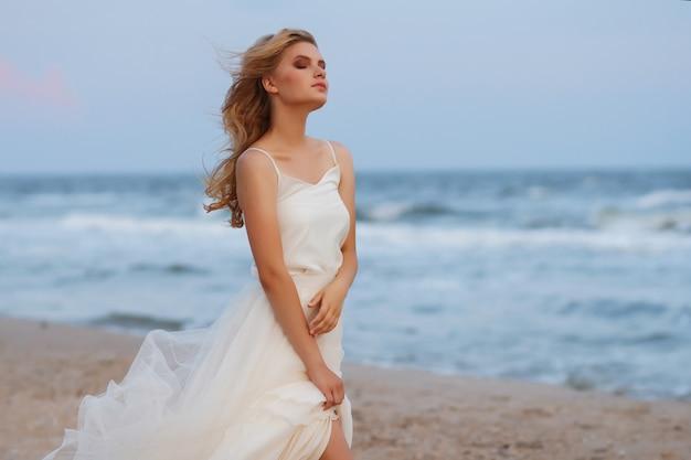 Ragazza romantica da sola sull'oceano. i suoi capelli si sviluppano nel vento, gli occhi sono chiusi. abito arioso bianco. sfondo sfocato.