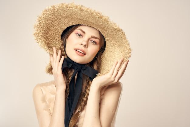 Ragazza romantica in abito beige e cappello di paglia con nastro nero emozioni ritratto di vista ritagliata modello
