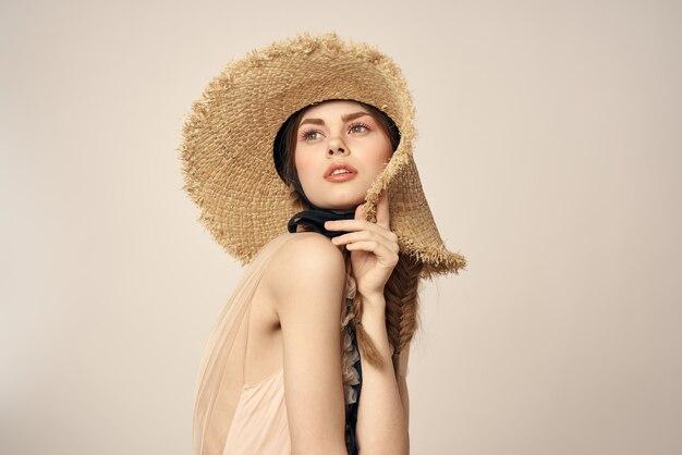 Ragazza romantica in vestito beige e cappello di paglia con il ritratto di emozioni del nastro nero del modello