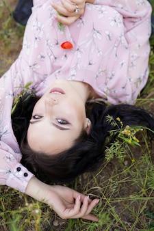 Ragazza romantica sdraiata sull'erba e tenendo il papavero fiore rosso