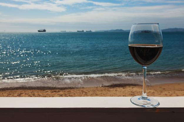 Romantico bicchiere di vino sulla ringhiera seduto sulla spiaggia in riva al vino rosso