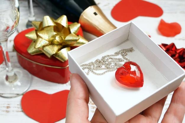Biglietto di auguri romantico con champagne e cuore rosso pendente come regalo