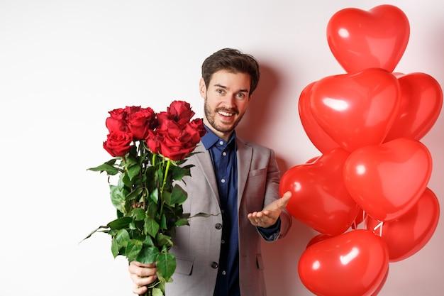Ragazzo romantico in vestito che dice buon san valentino, dandoti rose rosse e indicando la mano, in piedi con il regalo del palloncino cuore su sfondo bianco.