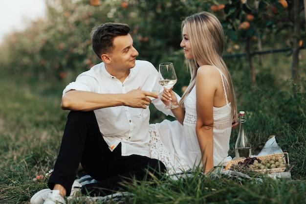 Coppie felici romantiche in vestiti bianchi che celebrano vacanza con vino al picnic.