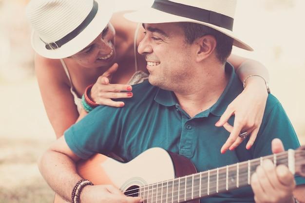 Abbraccio romantico e colori con persone allegre e felici di mezza età innamorate che suonano una chitarra insieme guardando e sorridendo
