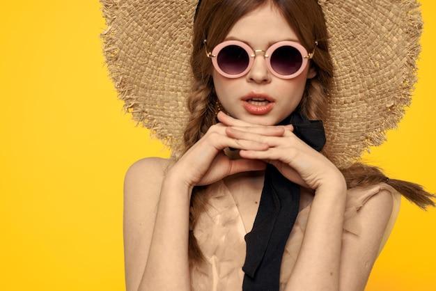 Signora romantica in cappello di paglia e occhiali da sole da portare