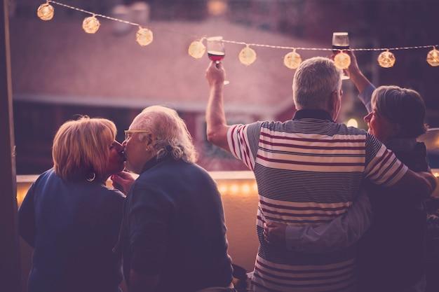 Concetto romantico e d'amore con due coppie di adulti anziani festeggiano insieme a casa in una terrazza con vista sulla città - brindando con vino e baci - le persone mature si divertono in amicizia all'aperto Foto Premium