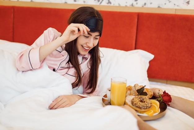 Coppia d'amore romantico, moglie felice che fa colazione con la rosa a letto a casa, buongiorno, marito premuroso. rapporto armonioso in famiglia