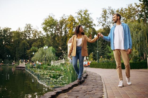 Coppie romantiche di amore che camminano allo stagno nel parco. l'uomo e la donna si rilassano all'aperto, prato verde. famiglia relax vicino al lago d'estate, weekend nella natura