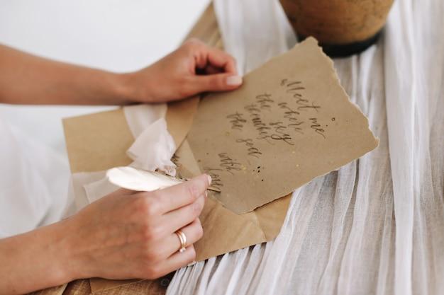 Lettera d'amore romantica con grafia vintage e busta e penna piuma sul tavolo