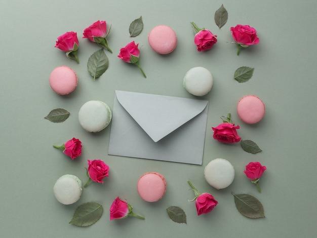 Romantica cornice incantevole da macarons e rose su sfondo verde. lay piatto. vista dall'alto