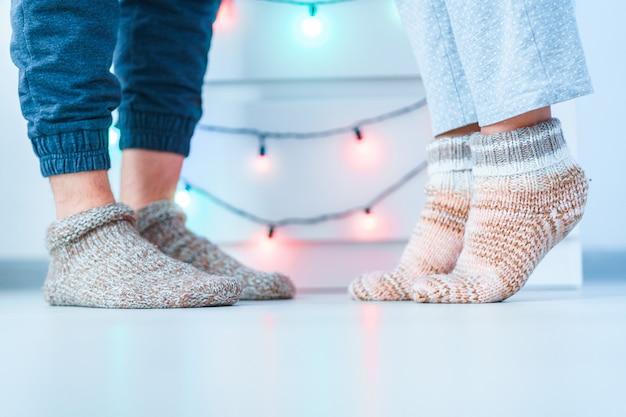 Coppie romantiche della famiglia degli amanti in calzini accoglienti molli tricottati caldi nell'orario invernale a casa.