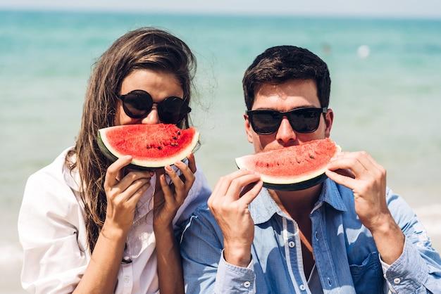 Giovani coppie degli amanti romantici che si rilassano tenuta e che mangiano una fetta di anguria sulla spiaggia tropicale e che guardano insieme vacanze estive