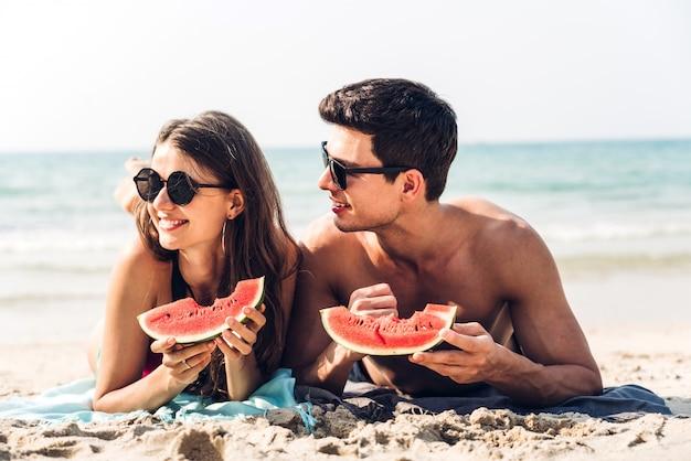 Giovani coppie degli amanti romantici che si rilassano tenuta e che mangiano una fetta di anguria sulla spiaggia tropicale vacanze estive