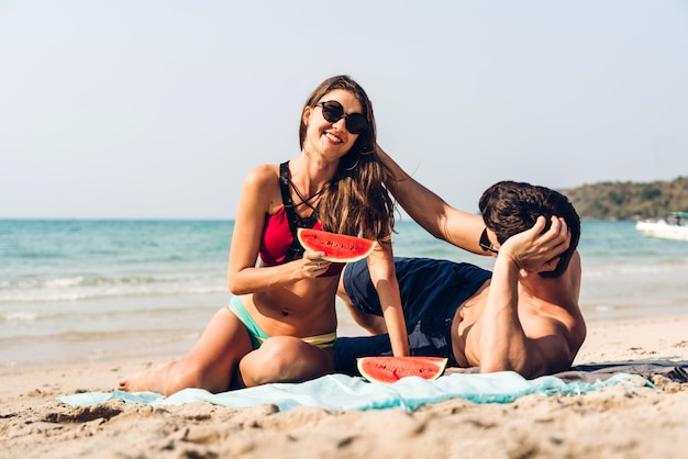 Giovani coppie romantiche degli amanti che si rilassano tenuta e che mangiano una fetta di anguria