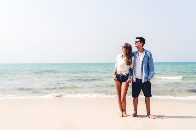 Le giovani coppie degli amanti romantici che si rilassano insieme sulla spiaggia tropicale equipaggi abbracciare con la donna e goda della vita vacanze estive