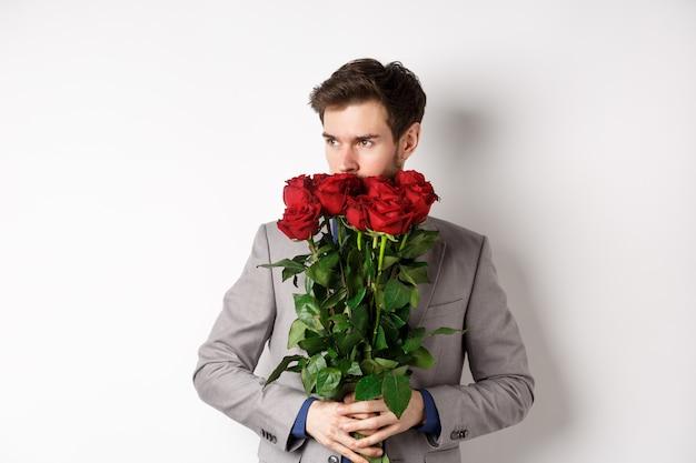 Uomo romantico in vestito odore di bouquet di rose e guardando pensieroso, in piedi su sfondo bianco. concetto di san valentino.