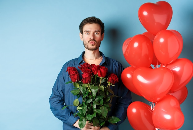 Uomo romantico con rose rosse e palloncini cuore rosso, labbra arricciate per bacio, facendo sorpresa il giorno di san valentino, in piedi su sfondo blu.