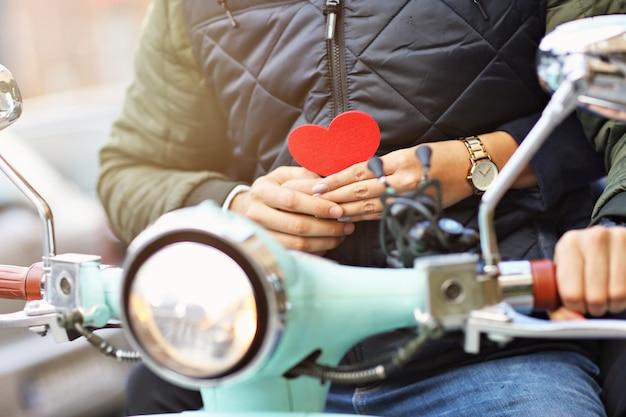 Sezione centrale romantica di giovane coppia in sella a uno scooter in autunno